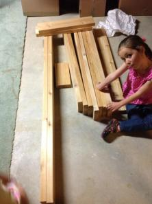 Gabi and the lumber, down in the basement, ready for construction.